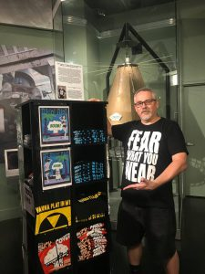 Artist Bradley Beard proudly standing next to his first wave of National Atomic Testing Museum t-shirts.